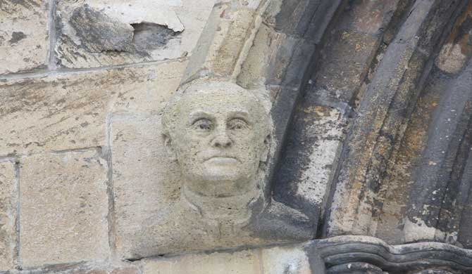 A carved face on a church wall.